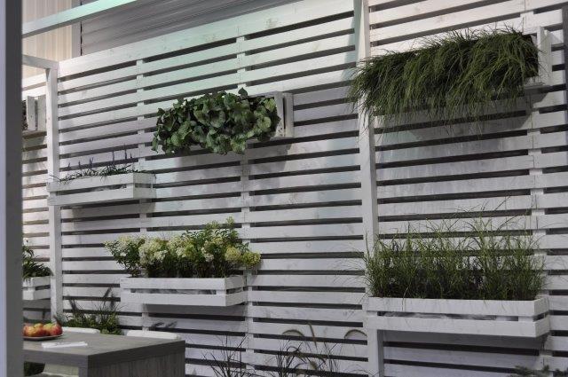 biała drewniana ażurowa ściana ze skrzynkami na rośliny