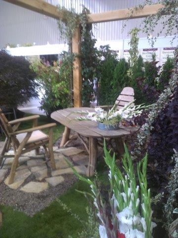 stół i krzesła z surowego drewna pod drewmianą pergolą