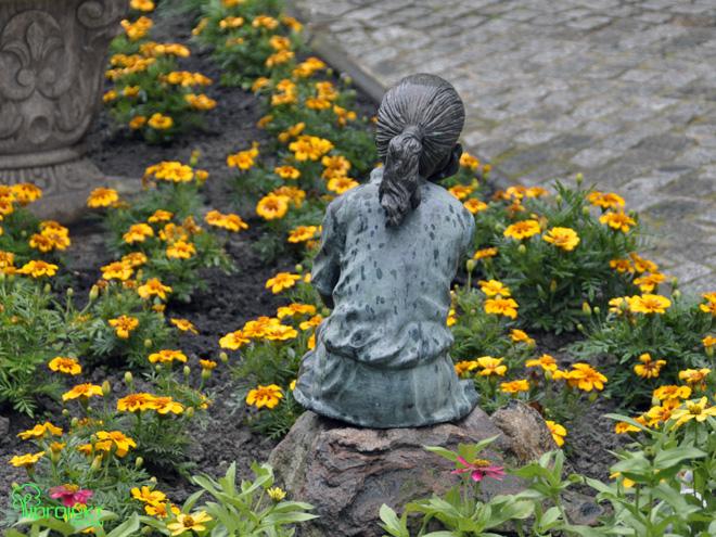 mosiężna postać zamyślonej dziewczynki ogród botaniczny IPROJEKT